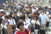 2000年7月8日、三宅島・雄山で噴火。その後も断続的に噴火が続き、三宅島は9月2日に全島民の島外避難指示を発令。火山灰の舞う中、島を離れる船に乗り込む人たち=東京都三宅村の三池港で2000年9月2日午後2時25分、森顕治撮影