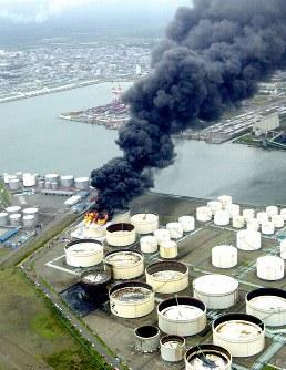 <十勝沖地震>2003年9月26日、北海道釧路沖でM8.0、十勝沖でM7.1の地震が相次いで発生。釣り人2人が行方不明に。負傷者約850人。住宅の全半壊約480棟。石油タンクの浮き屋根の上にナフサがあふれて燃え上がったり(奥)、石油製品が屋根上に露出したりした=苫小牧市の出光興産北海道製油所で2003年9月28日、本社機から山田耕司撮影