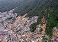 <広島土砂災害>猛烈な降雨の影響で、広島市で土石流などが発生。77人が死亡し、、住宅など400棟が全半壊した。写真は大雨による土砂崩れで、泥で埋まる市街地=広島市安佐南区八木で2014年8月20日午前11時すぎ、本社ヘリから望月亮一撮影