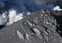 2014年9月27日、長野・岐阜両県にまたがる御嶽山(おんたけさん)が噴火。行楽シーズンの週末に発生したため多数の登山者が巻き込まれた。58人が死亡、5人が行方不明に。69人が負傷した。写真は御嶽山の山腹から吹き上げる噴煙のそばに建つ山小屋=長野県木曽町で2014年9月28日午前7時25分、本社ヘリから小出洋平撮影