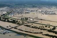 <西日本豪雨>2018年6月28日~7月8日、西日本を中心に全国的に広い範囲で記録的な大雨となった。特に6日夕から8日朝にかけて、気象庁は西日本の1府10県に大雨特別警報を発表し、最大限の警戒を呼び掛けた。豪雨による河川の氾濫、浸水、土砂災害による死者220人、行方不明10人、住宅の全半壊は約1万2000棟。写真は浸水した岡山県倉敷市真備町地区。手前は小田川=岡山県倉敷市真備町地区で2018年7月7日、本社ヘリから加古信志撮影