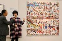 「ここから3」で自作の前に立ち「世界中の人たちに見てもらうために描いた」と力強く語る横溝さやかさん(右)=東京都港区の国立新美術館で2018年12月5日、岡本同世撮影