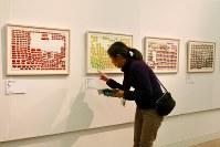 「ここから3」で自作のタイトルを確認する大倉史子さん。手前は「鮭」、一番奥が「しめさば」=東京都港区の国立新美術館で2018年12月5日、岡本同世撮影