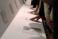 「ここから3」で、点字や凹凸によって漫画表現を伝える「触図」を試す来場者。背景に描かれたパーツごとに異なった感触になるよう工夫されている=東京都港区の国立新美術館で2018年12月5日、岡本同世撮影