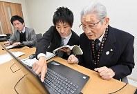 貸し出したドライブレコーダーの映像を見ながら警察官から指導を受ける森本一雄さん(右)=大阪市東住吉区で2018年11月16日、山崎一輝撮影