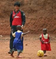 ルワンダでのサッカー教室で子供たちを笑顔で見つめる二村さんソルティーロ提供