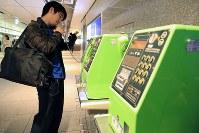 ソフトバンクの通信障害が起き、スマートフォンに記録された連絡先を見ながらJR東京駅近くの公衆電話から電話する男性=東京都千代田区で2018年12月6日午後6時33分、梅村直承撮影