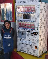 食用昆虫の自動販売機の前に立つ友田さん。「最初は罰ゲーム感覚で買ってもらいたい」と語る=熊本市中央区で2018年11月6日午後1時36分、中里顕撮影