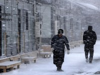 吹雪の中、仮設団地内を歩く人たち=北海道厚真町の表町公園仮設団地で2018年12月7日午前10時19分、貝塚太一撮影