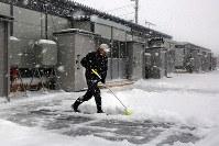 吹雪の中、仮設住宅の玄関前の雪かきをする被災者=北海道厚真町の表町公園仮設団地で2018年12月7日午前11時41分、貝塚太一撮影