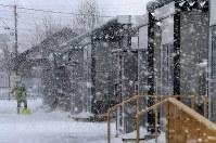 吹雪の中、雪かきをする被災者=北海道厚真町の表町公園仮設団地で2018年12月7日午前11時半、貝塚太一撮影