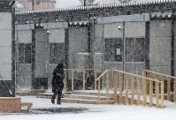 吹雪で仮設団地内を身をかがめて歩く人の姿があった=北海道厚真町で2018年12月7日午前9時48分、貝塚太一撮影