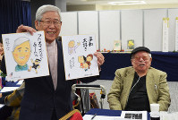 Hiroshi Sugibayashi, left, smiles as he shows illustrated paperboards drawn by Susumu Nishiyama, right, in the city of Fukuoka on Oct. 25, 2018. (Mainichi/ Takehiro Higuchi)