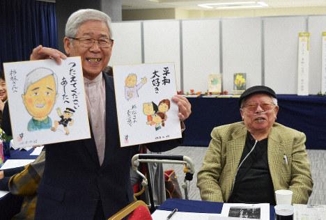 Hiroshi Sugibayashi, left, smiles as he shows illustrated paperboards drawn by Susumu Nishiyama, right, in the city of Fukuoka on Oct. 25, 2018. (Mainichi/ Takehiro Higuchi)