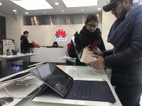 Foreigners look at a Huawei computer at a Huawei store in Beijing, China, on Dec. 6, 2018. (AP Photo/Ng Han Guan)
