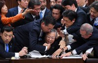 Opposition party legislators storm the seat of House of Councillors Judicial Affairs Committee Chairman Shinichi Yokoyama, center bottom, as the panel votes on a bill to revise the Immigration Control and Refugee Recognition Act on Dec. 8, 2018. (Mainichi/Naoaki Hasegawa)