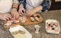 ベーコンを半分に切り、カキとプルーンをそれぞれ乗せて巻き、ようじで留める=尾籠章裕撮影