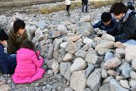 作業の後、石に思い思いの言葉を書く参加者=兵庫県宝塚市の武庫川の中州で、土居和弘撮影
