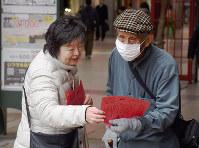 当時の「赤紙」を印刷したチラシを通行人に手渡すえひめ母親連絡会のメンバー(左)=松山市の大街道商店街で、中川祐一撮影
