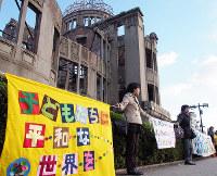 それぞれの思いを込めたバナーを手に原爆ドームを囲む参加者ら=広島市中区で、寺岡俊撮影