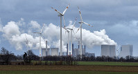 Renewable and fossil-fuel energy is produced when wind generators are seen in front of a coal fired power plant near Jackerath, Germany, on Dec. 7, 2018. (AP Photo/Martin Meissner)