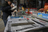 A man arranges magazines near newspapers with the headlines of China outcry against U.S. on the detention of Huawei's chief financial officer, Meng Wanzhou, at a news stand in Beijing, on Dec. 10, 2018. (AP Photo/Andy Wong)