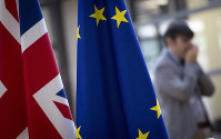 In this Nov. 14, 2018 file photo, a journalist speaks on his phone as he passes by the Union Flag, left, and the EU flag at the Europa building in Brussels. (AP Photo/Virginia Mayo)