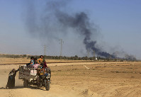 In this April 4, 2016 file photo, smoke rises as people flee their homes during clashes between Iraqi security forces and members of the Islamic State group in Hit, Iraq. (AP Photo/Khalid Mohammed)
