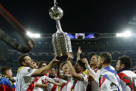 Payers of Argentina's River Plate celebrate with the trophy after defeating 3-1 Argentina's Boca Juniors in the Copa Libertadores final soccer match at the Santiago Bernabeu stadium in Madrid, Spain, on Dec. 9, 2018. (AP Photo/Manu Fernandez)