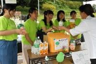 大阪府河内長野市の「奥河内くろまろの郷」でのインターンシップで、来場者に飲み物を手渡す帝塚山学院大の学生たち=9月1日、関野正撮影