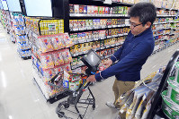 Items are purchased on the spot at Trial Company's Quick Onojo location using a cart affixed with a tablet, in Onojo, Fukuoka Prefecture, on Dec. 11, 2018. (Mainichi/Michiko Morizono)