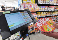 A tablet affixed to carts at Trial Company's Quick Onojo location, which allows customers to pay for products on the spot, is seen in Onojo, Fukuoka Prefecture, on Dec. 11, 2018. (Mainichi/Morizono)