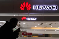 In this Dec. 6, 2018 photo, a man lights a cigarette outside a Huawei retail shop in Beijing. (AP Photo/Ng Han Guan)