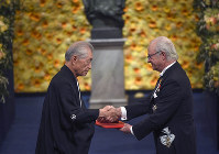 Physiology or medicine laureate Tasuko Honjo, left, receives the prize from King Carl Gustaf of Sweden, during the Nobel Prize award ceremony, at the Stockholm Concert Hall, in Stockholm, on Dec. 10, 2018. (Pontus Lundahl/Pool Photo via AP)