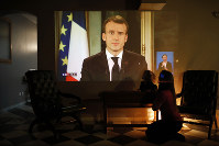A woman and her daughter watch French President Emmanuel Macron during a televised address to the nation, in Lyon, France, on Dec. 10, 2018. (AP Photo/Laurent Cipriani)