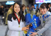 Figure skater Rika Kihira, left, receives a bouquet upon her arrival at Narita International Airport in the city of Narita, Chiba Prefecture, on Dec. 11, 2018, after she won the Grand Prix of Figure Skating Final in Vancouver. (Mainichi/Koichiro Tezuka)