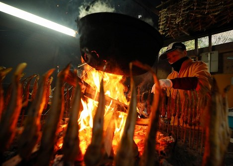 竹串に刺したハゼをいろりで焼く榊照子さん。焼き終わった後はわら縄で作業場内に吊し、煙でじっくりといぶす=宮城県石巻市で2018年12月6日午前9時22分、喜屋武真之介撮影