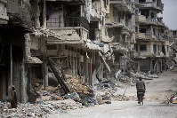 In this June 5, 2014, file photo, a man rides a bicycle through a part of Homs, Syria, devastated by the country's civil war. (AP Photo/Dusan Vranic)