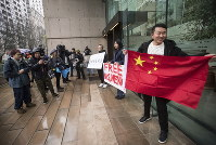 Supporters hold signs and a Chinese flag outside the British Columbia Supreme Court in Vancouver during the third day of a bail hearing for Meng Wanzhou, the chief financial officer of Huawei Technologies, on December 11, 2018. (Darryl Dyck/The Canadian Press via AP)