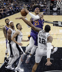 Phoenix Suns forward Richaun Holmes (21) drives to the basket against San Antonio Spurs forward LaMarcus Aldridge (12) during the first half of an NBA basketball game, on Dec. 11, 2018, in San Antonio. (AP Photo/Eric Gay)