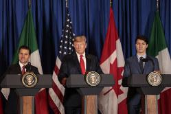 新貿易協定に調印する米加メキシコの首脳。中央がトランプ米大統領(Bloomberg)