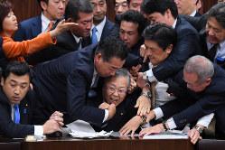 参院法務委員会の入管法改正案採決で横山信一委員長(中央)に詰め寄る議員ら(12月8日)