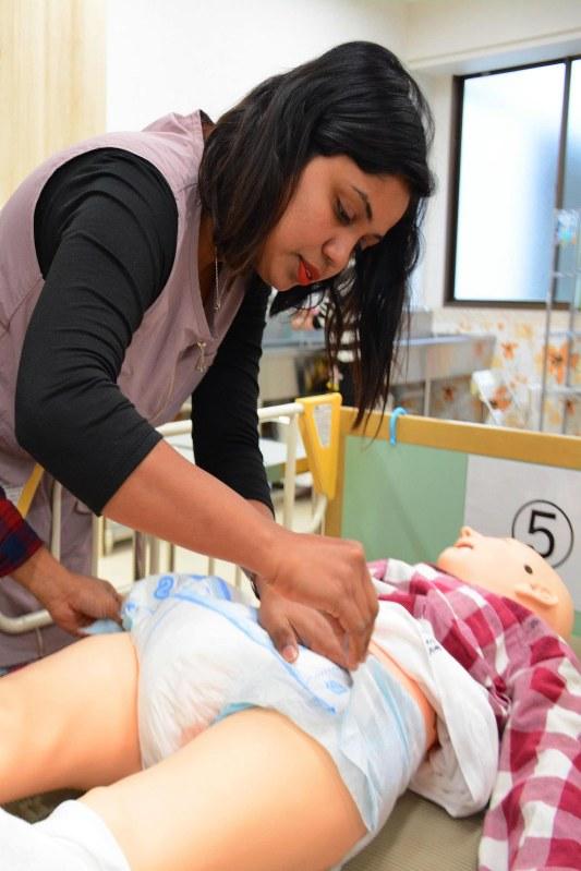 人形を使ってオムツ交換の練習をする外国人留学生