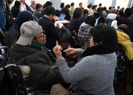 At an informational gathering after the trial hearing, a woman, right, explains to a man the report by the legal team representing the plaintiffs in Japanese Sign Language, in Osaka's Kita Ward, on Dec. 12, 2018. (Mainichi/Rei Kubo)