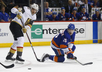 New York Islanders right wing Cal Clutterbuck (15) plays the puck against Vegas Golden Knights left wing Tomas Nosek during the second period of an NHL hockey game, on Dec.12, 2018, in New York. (AP Photo/Noah K. Murray)