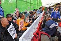 People sit for a protest against land reclamation work to build a new U.S. military base off the Henoko coast in front of the gate to U.S. Marine Corps Camp Schwab in the city of Nago, Okinawa Prefecture, on Dec. 14, 2018. (Mainichi/Takeshi Noda)