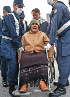 A woman in a wheelchair shouts during a protest against land reclamation work to build a new U.S. base while she is removed by police officers, in front of the gate to U.S. Marine Corps Camp Schwab, in the city of Nago, Okinawa Prefecture, on Dec. 14, 2018. (Mainichi/Takeshi Noda)