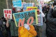 Demonstrators raise their voices against land reclamation work to build a new U.S. base off the Henoko coast, in front of the fences of U.S. Marine Corps Camp Schwab, in the city of Nago, Okinawa Prefecture, on Dec. 14, 2018. (Mainichi/Takeshi Noda)