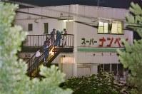 <八王子スーパー3人射殺事件>1995年7月30日、東京都八王子市のスーパー2階の事務所で、女子高生2人を含むアルバイト店員ら3人が射殺された。警視庁は強盗殺人事件とみて捜査。殺人罪などの公訴時効を廃止する10年の刑事訴訟法改正により、捜査が継続している。写真は3人が射殺されたスーパーナンペイの2階事務所付近を調べる捜査員ら=東京都八王子市大和田町で1995年7月31日撮影