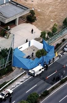 <神戸小学生連続殺傷事件>神戸市で小学4年の女児と小学6年の男児が相次いで殺害され、他の小学生3人がナイフで切られるなどしてけがをした事件で、兵庫県警は1997年6月28日、中学3年の少年(14)を逮捕。男児の遺体の一部は「酒鬼薔薇聖斗」の犯行声明と一緒に中学校の校門前で発見された。子供を襲った残忍な事件が中学生の非行だったことに波紋が広がった。写真は殺害された小学6年男児の遺体の一部が発見された中学校の校門付近=神戸市で1997年5月27日、本社ヘリから撮影